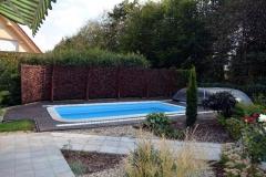 Dřevoplast kolem bazénu ladí s tmavým proutěným plotem